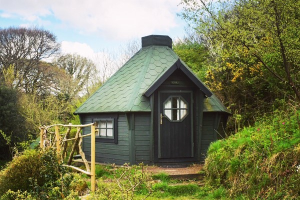 Green hobbit hut amongst the trees at Acorn Camping in Cornwall