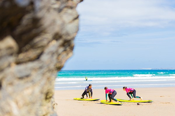Two people doing a surf lesson in Cornwall taught by an experienced instructor